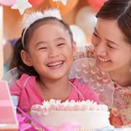 Birthday girl smiles in front of cake
