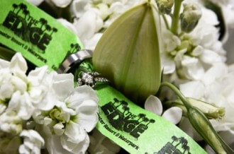 Edge Waterpark wristband fed through two wedding rings, surrounded by flowers