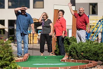 Group of four adults plays outdoor mini golf