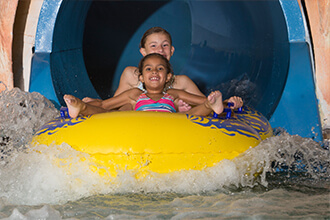 Two girls on a two-person tube come out of a waterslide