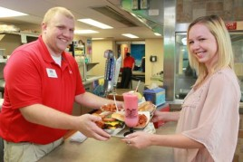 Man serving woman pizza and a smoothie