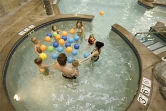 Six kids and two adults play with plastic balls in vortex pool
